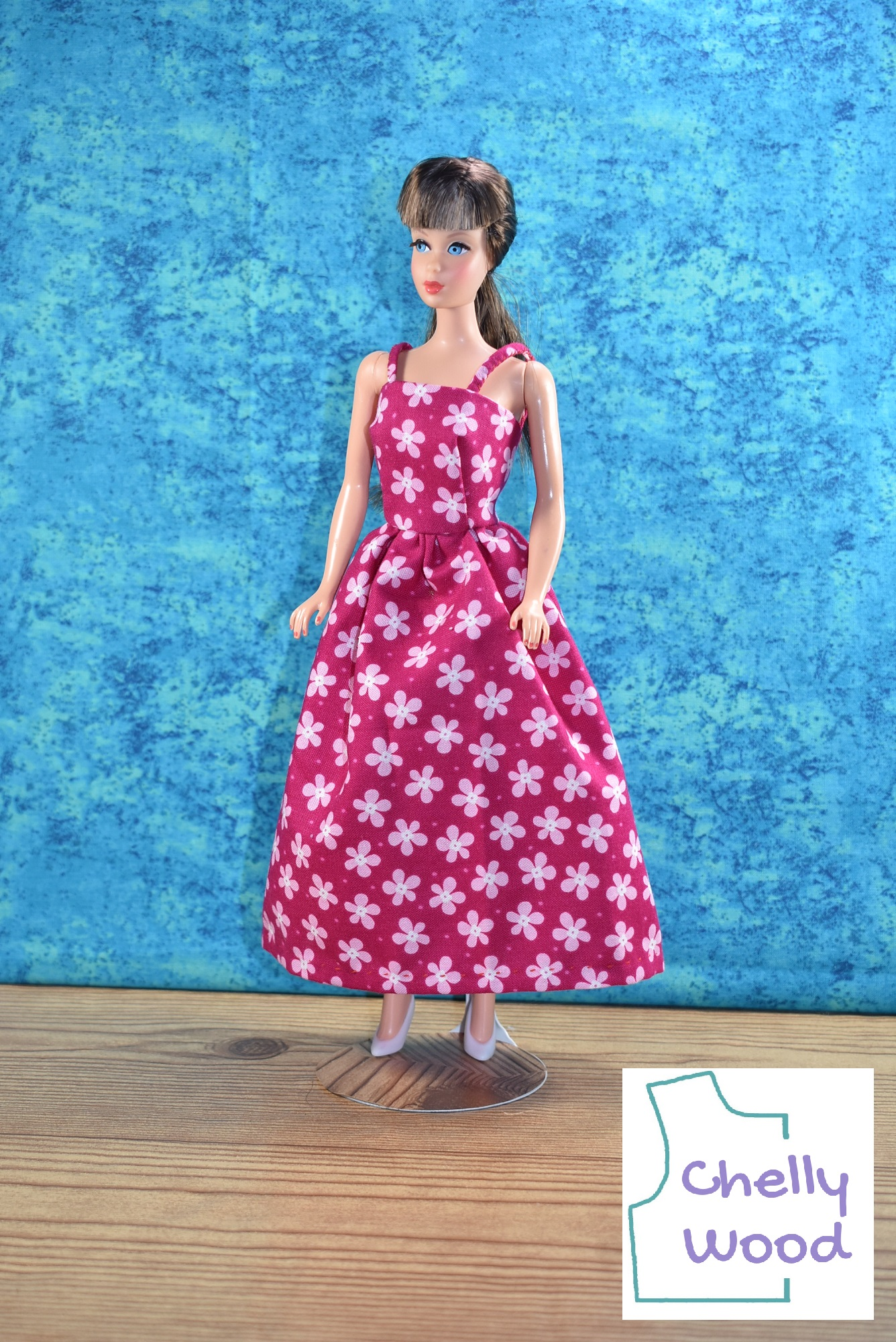 """The image shows a vintage Barbie modeling a hot pink sundress with straps (aka sun dress). The bright pink cotton fabric is dotted with tiny pale pink flowers that have white centers. She wears tiny white plastic high-heel shoes. This is a Mattel vintage Barbie with long dark brown hair and bangs. Her hair is pulled back in a pony tail. There's a watermark on the image, and it's the outline of a bodice pattern with the name """"Chelly Wood"""" inside the shape of the pattern. That's because ChellyWood.com is a website best known for its free printable PDF sewing patterns for making doll clothes to fit dolls of many shapes and all different sizes. If you'd like to make this strappy floral sundress, please click on the link in the caption. Follow the links to the page with the free patterns and tutorial videos."""
