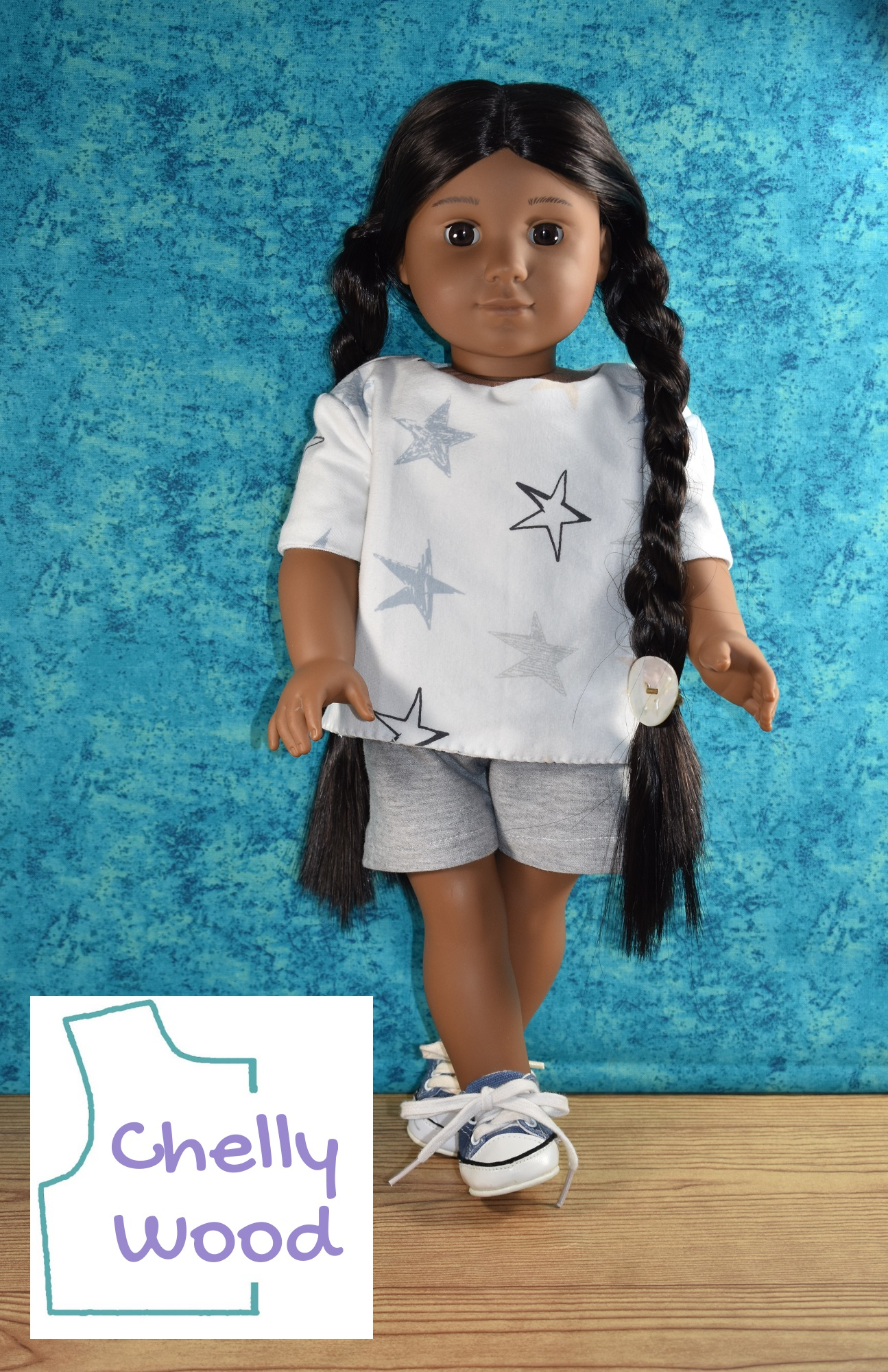 American Girl Kaya doll stands with her feet crossed at the ankles. She wears a handmade tee shirt with a blue and grey star pattern on the jersey fabric it is made with. Her shorts are made of grey jersey fabric to nicely coordinate with the grey stars on her white shirt. Would you like to make this outfit for your 18 inch dolls? Please visit ChellyWood.com for the free printable PDF sewing patterns.
