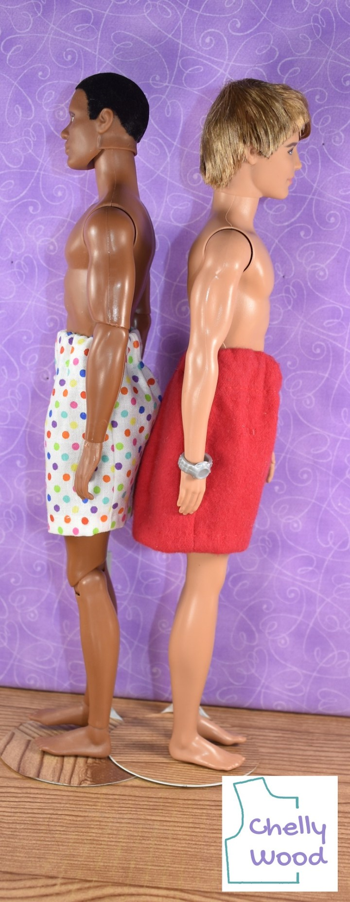 An articulated Texas A and M doll (African American version) stands back to back with a regular Ken doll with blond hair. The African American Ken is wearing a pair of multicolored polka dot boxers while the blond Ken is wearing a pair of red flannel boxers. Blond Ken wears a silver watch.