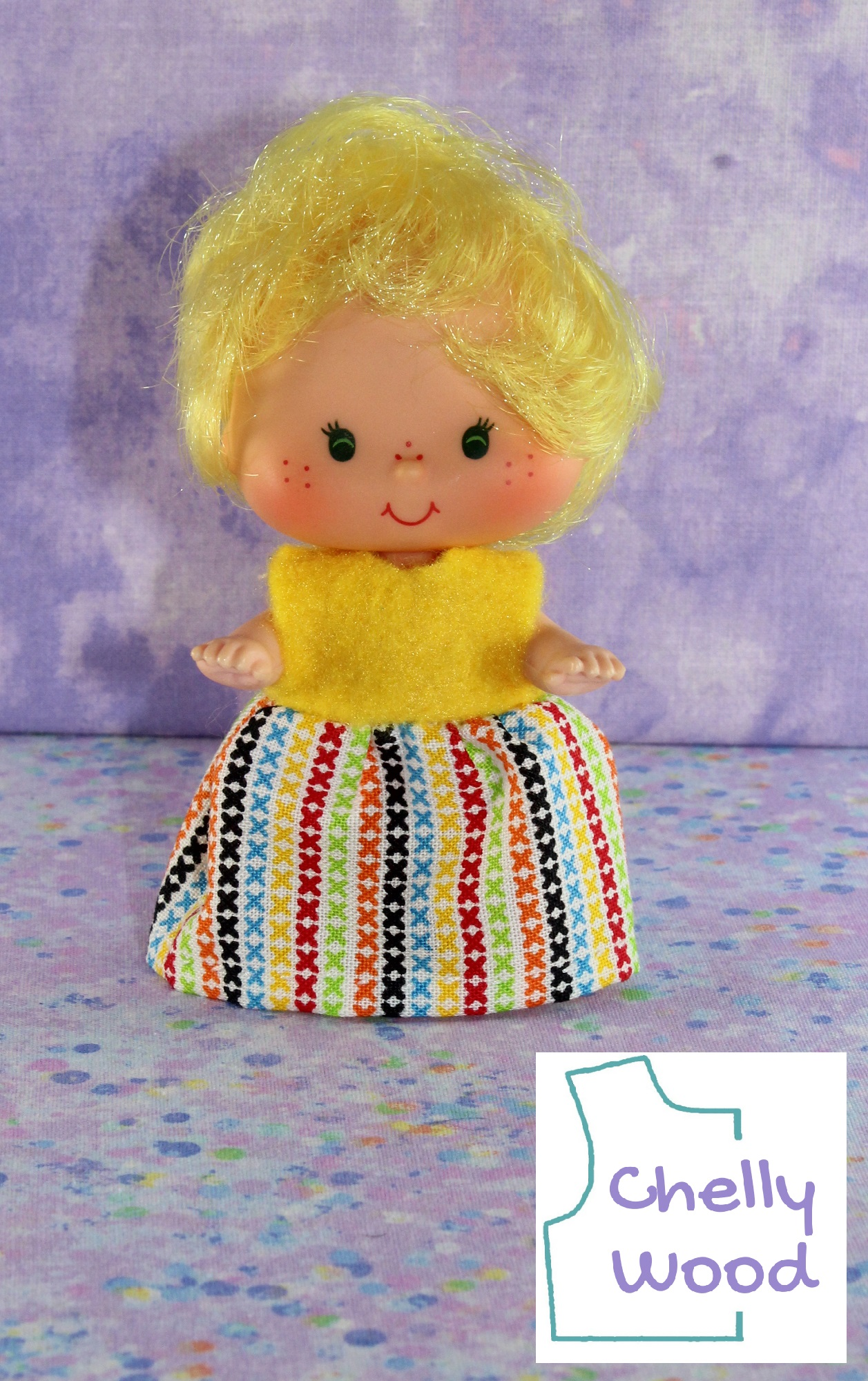The image shows a Strawberry Shortcake toddler doll (Lemon Meringue) wearing a handmade dress. Free doll clothes patterns for making this dress are found at ChellyWood.com