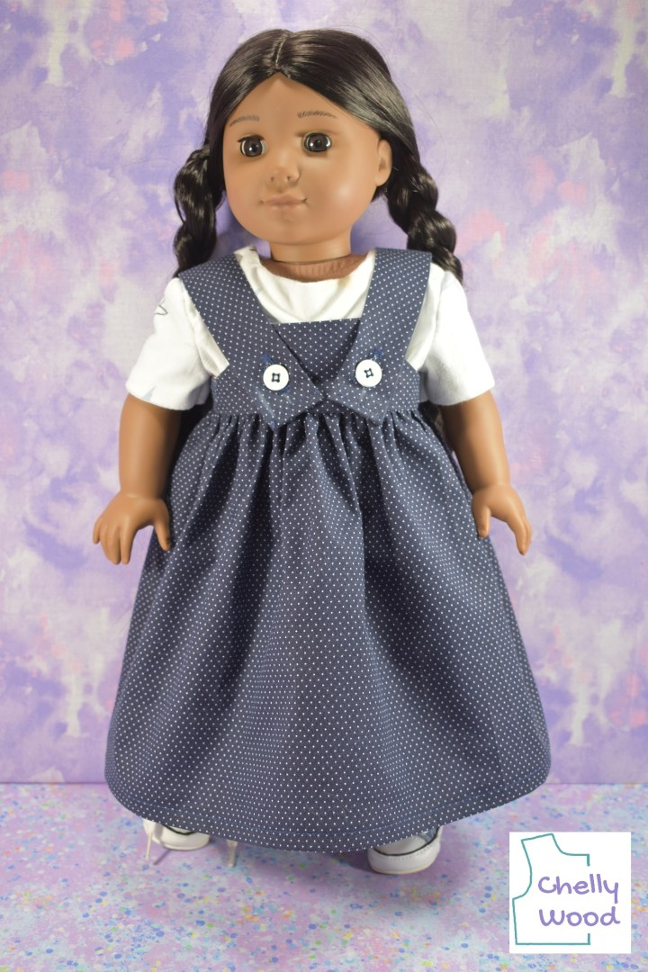 This is a studio photograph of the American Girl Kaya doll in a dress with straps that close with buttons over a pinafore style bodice. The skirt is quite long -- almost floor length -- and under her AG dress with straps, she wears a simple white tee shirt. The dress itself is made of blue dotted Swiss cotton fabric, and the buttons are 5/8 inch white plastic buttons that close the long straps over the front of the dress. The AG doll is Kaya, a Native American girl with braids in her long hair. The shoes poking out from under this pinafore or sundress style dress appear to be comfortable sneakers.