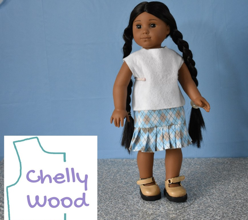 The image shows an American Girl Kaya doll modeling a pale blue, tan, and white argyle print cotton skirt with a knife pleated ruffle, and a simple sleeveless felt shirt. She wears patent leather Mary Jane shoes. The background behind her is a blue sky with a concrete slab she appears to be standing on. The watermark reminds us to go to Chelly Wood dot com for all the free printable PDF sewing patterns and tutorial videos we will need to enjoy sewing this outfit for 18 inch dolls like American Girl, Adora Amazing Girls, Madame Alexander dolls, Journey Girls, and more in this size range.