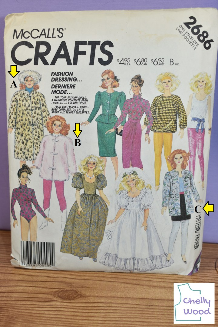 """In this image, we see the photo of McCall's Craft Pattern number 2686 from Chelly Wood's vintage doll clothes pattern collection. These outfits are reminiscent of styles from the 1980's. Chelly has marked the image in the upper left corner with a letter A, and that image could be described as a bulky, calf length fur coat with a Russian style fur hat. She has marked the next image to the right with a letter """"B."""" This image could be described as a doll wearing stretch pants, white boots, and a very bulky thigh-length pink fur coat. Another of the marked images (letter """"C"""") is more of a business suit with a jacket that has no lapels but comes down to the upper thigh level of the doll. Under this print fabric jacket she wears a mini skirt and shirt. Now among the other outfits offered on this pattern are (clockwise from the top center), a puff sleeve, knee length dress with ruffle at the waist; a body suit with wrap-around skirt; a sweat shirt with stretch pants; a tank top with sash and stretch pants; a wedding gown with short puff sleeves and a neckline ruffle; a prom dress with short puff sleeves and no ruffle; and the turtle neck body suit by itself."""