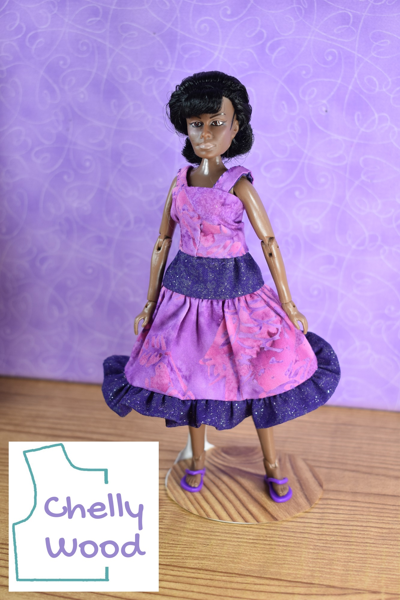 In this photograph, we see the Lieutenant Uhura action figure from Mego dressed in handmade doll clothes that include a reversible tank top (pink on one side and purple on the other side) and a three tier skirt layered in first purple glittery cotton then pink batik cotton then a purple glittery cotton ruffle. The doll's hair is perfectly styled (like the real Nichelle Nichols) and she wears tiny purple plastic flip flop shoes.