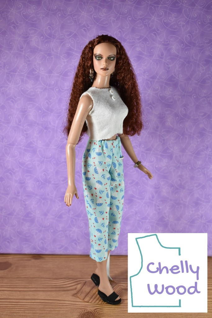 The photograph shows a Tonner doll with dark makeup and wavy auburn hair wearing handmade pajamas: a felt sleeveless shirt with front darts and a pair of elastic waist pajama pants that are cut short at the shin. The shirt is made of solid white craft felt and has tiny buttons down the front (for aesthetic value more than functionality). It also has an embroidery edge along the sleeve and collar with a simple whipstitch. The pajama pants are made of blue cotton fabric decorated with tiny anchors and sailboats. If you'd like to access the free printable PDF sewing patterns for making these pajamas, please click on the link in the caption.