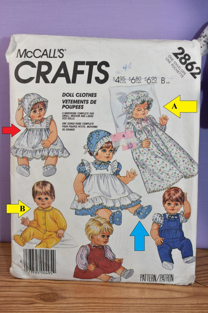 """Here we see a close-up of McCall's Crafts Pattern number 2862 for baby doll clothes in small, medium, and large doll sizes. There are colored arrows superimposed over the patterns. Clockwise, starting at one o'clock, we see a yellow arrow labeled """"A"""" pointing at a baby doll in a long-sleeved nightgown with a ribbon tied around the neck and a Martha Washington-style nightcap. At five o'clock, we see a baby doll in a pair of overalls with a front pocket and a puff sleeve shirt underneath; there's no arrow pointing to this doll. At six o'clock we see a baby doll in an overalls-style dress with long puff sleeves; again, there's no superimposed arrow pointing at this doll. At seven o'clock we see a baby doll in footie pajamas with long sleeves; a yellow arrow marked """"B"""" points at this doll. At eleven o'clock we see a baby doll in a pinafore style dress with ruffles at the arms and at the bottom of the dress (she also wears a bonnet); a red arrow points at this baby doll. In the center of all of these dolls is a baby doll wearing a blue bonnet, a blue dress, and a white pinafore (she also wears little blue bootie shoes); there's a blue arrow pointed at her booties. The photo of this pattern comes from ChellyWood.com, a free doll clothes pattern website, where a discussion about baby doll pajama patterns and their variations accompanies this image."""