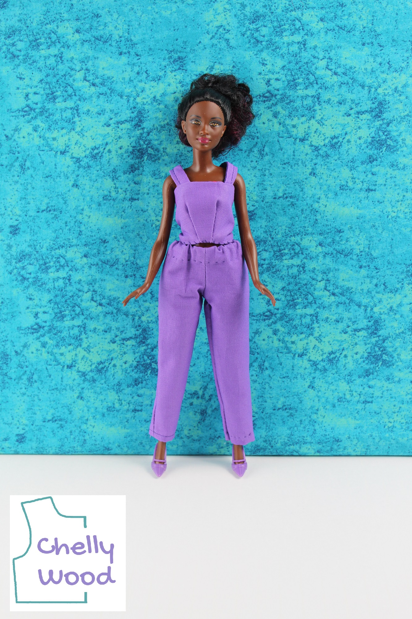 A lovely African or African American Barbie with light brown eyes and a chocolate complexion stands before a turquoise blue watery colored swatch of fabric. Her purple clothes sharply contrast against the background turquoise blue color. She stands in high heel purple plastic shoes with her feet spread slightly apart. She wears a medium purple cotton pair of elastic waist ankle pants and a matching purple cotton tank top with cotton straps. The tank top has darts. The watermark reminds us that you can find free printable PDF sewing patterns for making these Petite Barbie doll clothes at ChellyWood.com