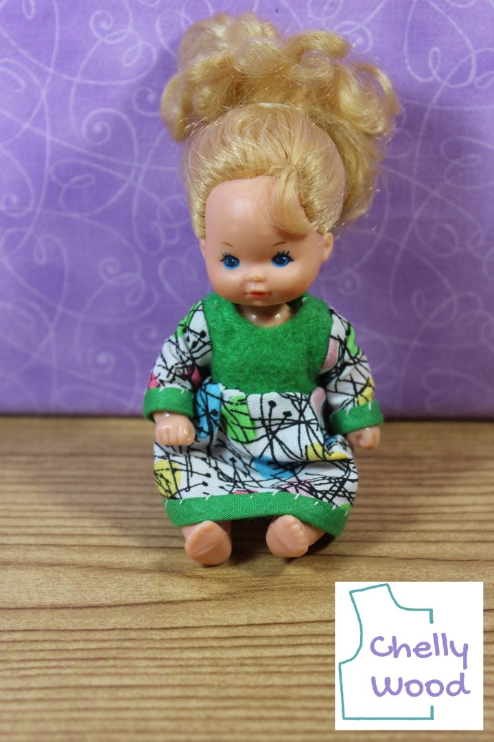 Here we see a Heart Family baby doll from the Barbie family set from the 1980s. The tiny baby doll has her hair pulled up in a high pony tail. She wears a handmade dress with a green felt bodice, green bias tape cuffs, and around the bottom of the dress's skirt, there's green bias tape trim. The long sleeves and skirt of the dress are made of multicolored tiny Easter egg printed fabric with black lines criss-crossing the fabric in an almost spiderweb way.