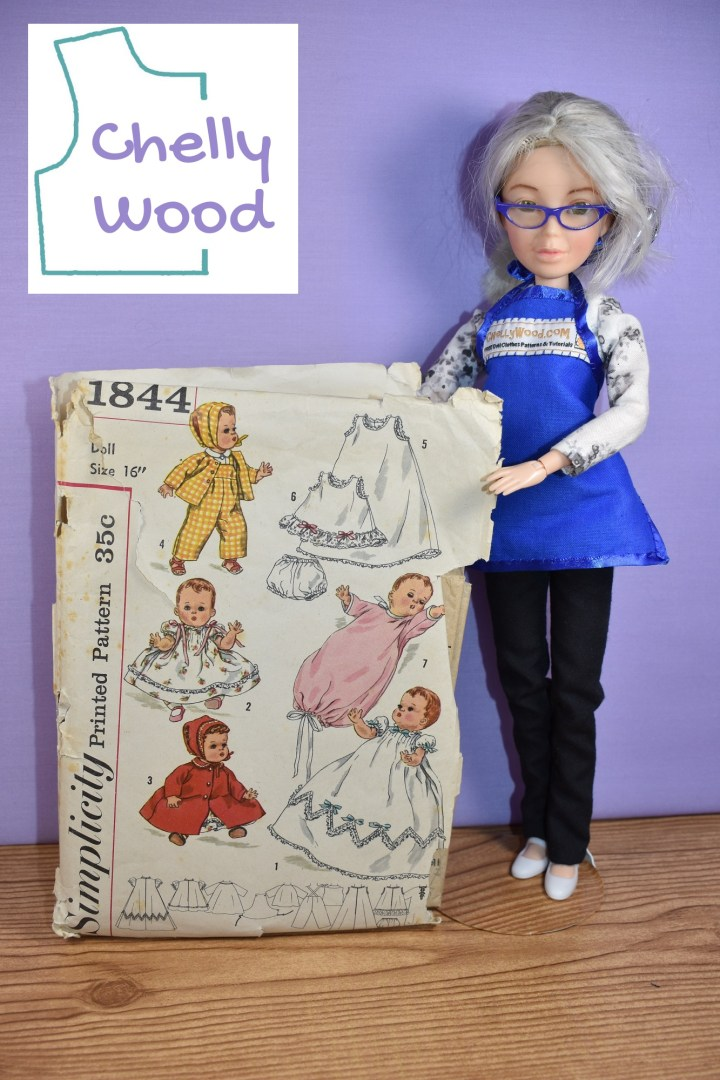 The image shows the Chelly Wood doll (a Spin Master Liv doll that has been re-designed to look like the real doll clothing designer, Chelly Wood, with her white hair up in a bun and her blue apron over a white shirt and black trousers) -- she stands holding up a truly vintage pattern for the Simplicity 16 inch baby doll clothes pattern number 1844, which was published in or around 1956 (the copyright date). The front of the pattern says it will fit dolls that are 16 inches tall.