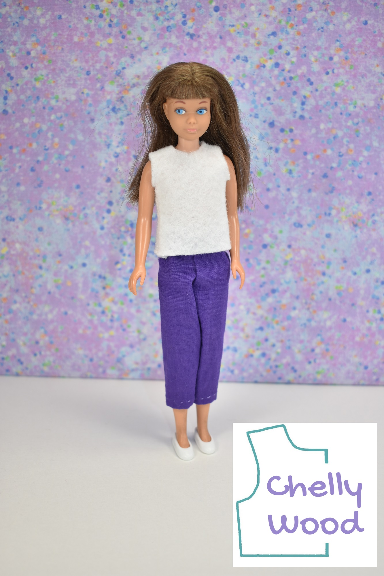 In this photo, we see a brunette vintage Skipper doll modeling hand made doll clothes: a pair of pedal pusher pants or capris and a felt shirt. She also wears plastic shoes. The doll faces toward the camera with slightly right-glancing eyes. In the lower right hand corner is the Chelly Wood logo, indicating that the free printable PDF sewing patterns and tutorial videos for making these doll clothes can be found at ChellyWood.com