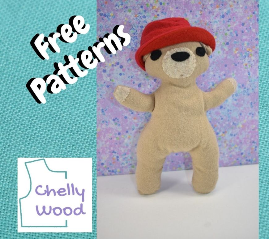 """On a turquoise blue square of linen fabric, we see a photograph of a small tan bear wearing a cute red hat with a turned-up brim. The overlay says """"free patterns"""" and the watermark reminds us to go to ChellyWood.com for free printable PDF sewing patterns for making the stuffed animal shown here, along with his Paddington-bear-like hat."""