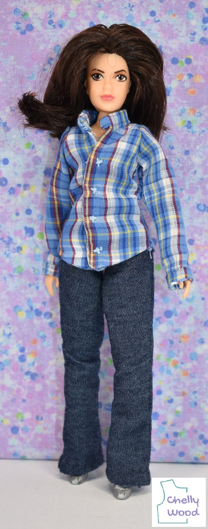 This photo shows the Mego action figure that looks like Piper from the show Charmed (CBS) wearing handmade western style doll clothes. Her shirt is a blue plaid shirt with white, yellow, and red stripes blending throughout the blue of the shirt. This long sleeved plaid shirt has a collar and cuffs. Beneath her shirt, she wears a pair of rustic looking dark blue denim elastic waist jeans that have a boot cut leg. Her silver high heel shoes keep her pants from brushing the white floor beneath her just barely. Behind her is a light purple backdrop with tiny spots in blue, yellow, green, and light orange. Her full head of hair arches above her brow and curls slightly above her right shoulder.
