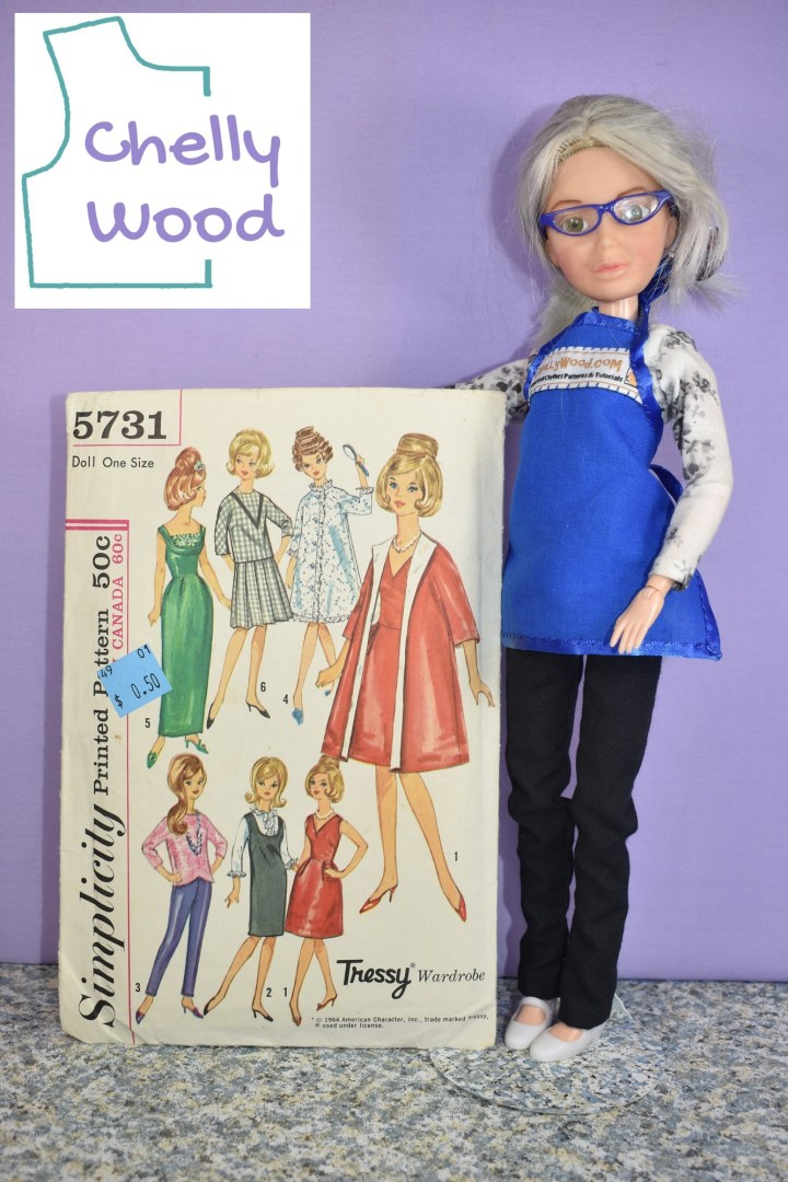 """In this image, the Chelly Wood doll (a Spin Master Liv doll that has had her face repainted and her wig dyed grey to look like the real doll clothing designer, Chelly Wood) holds up Simplicity """"Tressy"""" doll clothes pattern number 5731 with 7 different doll clothing items pictured on the front of the pattern."""