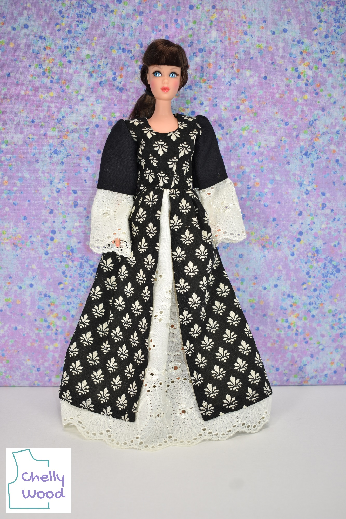 """In this photograph, a Vintage Barbie models a Renaissance princess-style ball gown or long dress. She has dark brown hair with bangs (or fringe in the UK). Her sleeves are long with two layers; the under-side layer is made of cream eyelet lace and the sleeve over the top is made of solid black fabric. The dress also has a petticoat made of cream colored eyelet fabric. This is visible at the front of the dress, as the upper layer of skirt is split from the navel down to the floor. The bodice and top layer of skirt are made of black cotton fabric printed with tiny """"fleur de lis"""" patterns like a Renaissance era dress that had been embroidered or woven as a tapestry. The watermark on this image reminds us that the free printable PDF sewing pattern and tutorial videos for making this dress can be found at Chelly Wood dot com."""