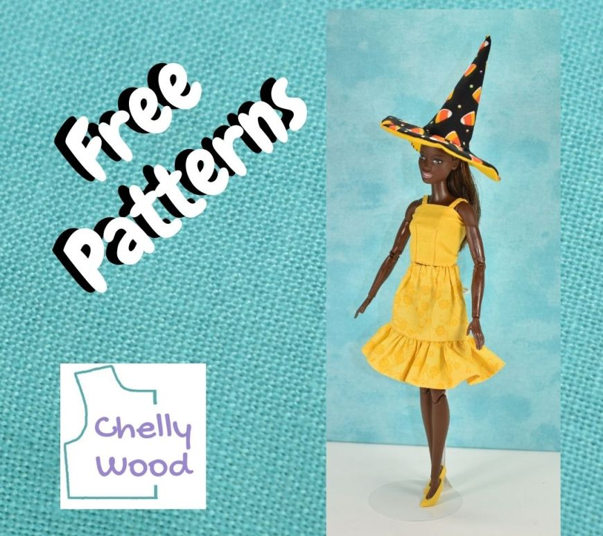 """On a turquoise blue frame, a Barbie models her pretty yellow doll clothes and her black witch's hat. She looks like she's ready to attend a Halloween party, but she's almost too sunshine-pretty to be dressed for Halloween! The words on the framed image say """"free patterns,"""" and """"Chelly Wood."""""""