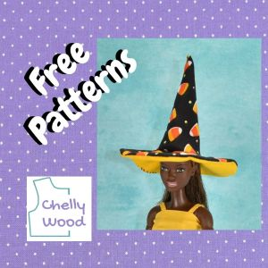 """On a purple polka dot fabric frame, we see the words """"free patterns,"""" along with the Chelly Wood logo and an image of a Made to Move African or African American Barbie modeling a pointed witch hat made of fabric and craft foam."""