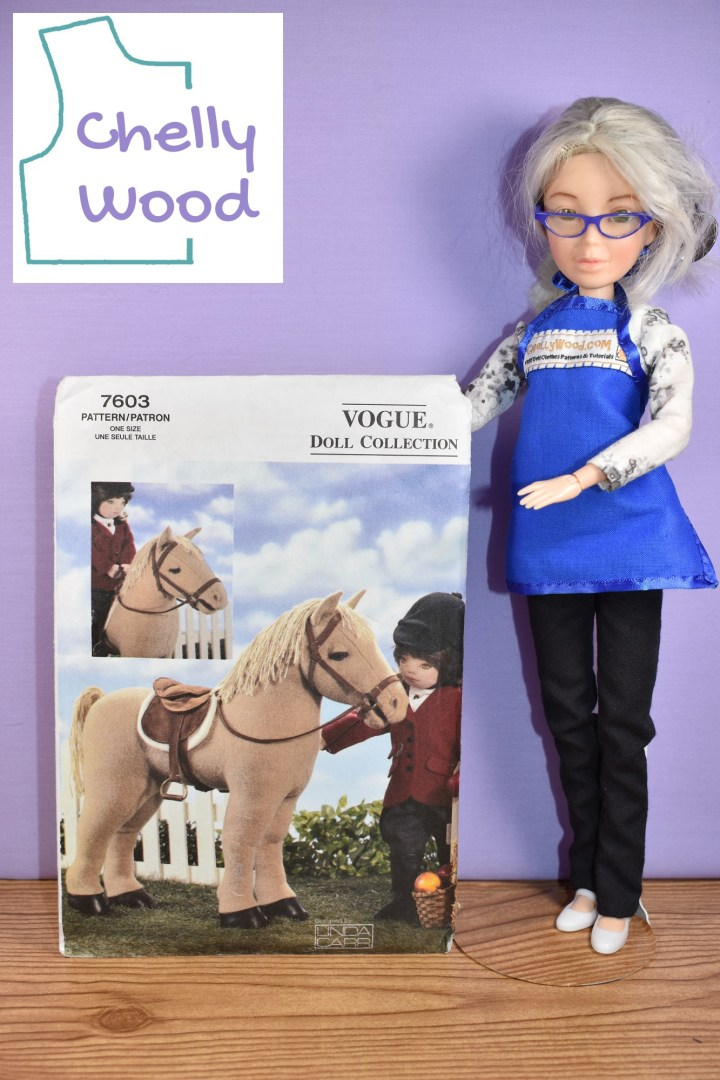 The image shows the Chelly Wood doll (a Spin Master Liv doll that has been altered to look like the real doll clothing designer, Chelly Wood) holding up Vogue 18 inch doll's plush horse pattern number 7603. The photo on the cover of the Vogue 7603 doll collection pattern shows a plush 18 inch doll dressed in formal riding gear and standing next to a plush horse with a yarn mane, a saddle, bridle, and saddle blanket, all of which appear to be handmade. In one corner of the image we see the Chelly Wood logo, reminding us that the discussion about how to turn this plush horse toy pattern into a stick horse can be found at Chelly Wood dot com.