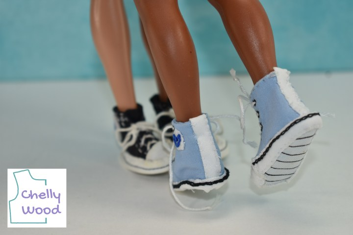 In the distance, we see a a pair of black Converse high top sneakers. In the foreground, a blue pair of sneakers is worn by a different doll, but the doll is lifting one of her feet into the air so we can see that her light blue sneaker has a black and white striped tread underneath. The ChellyWood.com logo appears in the bottom of this image.