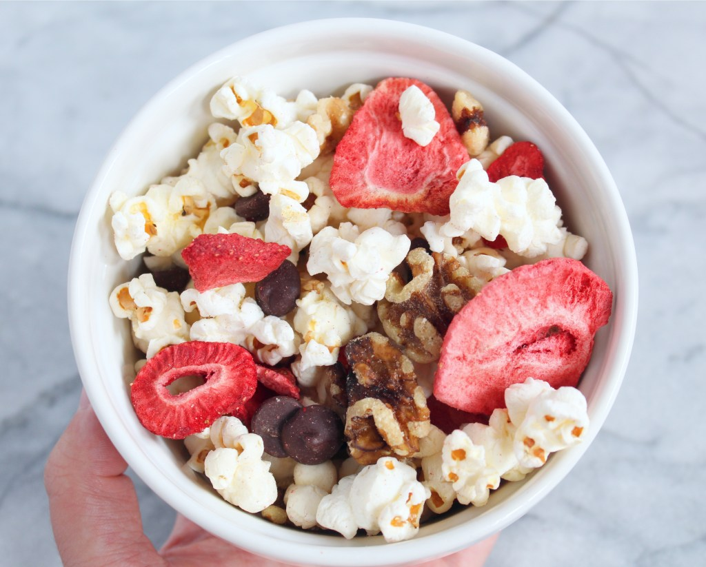 Healthy popcorn trail mix is the perfect snack for any event and every taste-bud. Customize yours by making it sweet, salty, or savory. For those of you with a sweet tooth, this popcorn, walnut, dried strawberry, and dark chocolate chip combo is a game changer!
