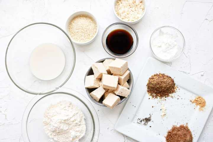 Numerous white and clear bowls filled ingredients such as flour, coconut shreds, liquid aminos, and tofu