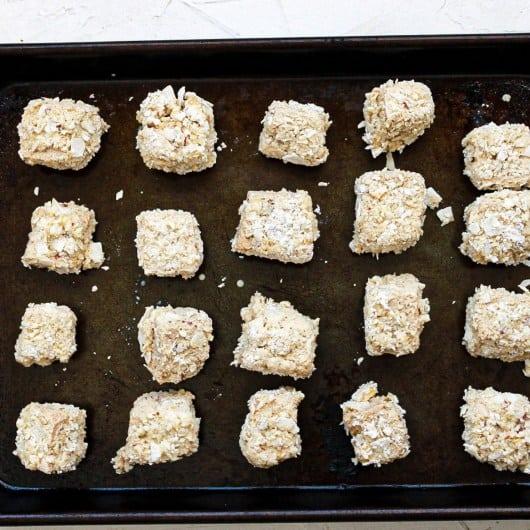 Coconut crusted tofu pre fried sitting on a dark baking sheet