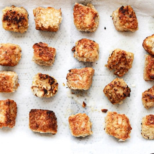 golden brown Tofu cubes after being fried on a paper towel