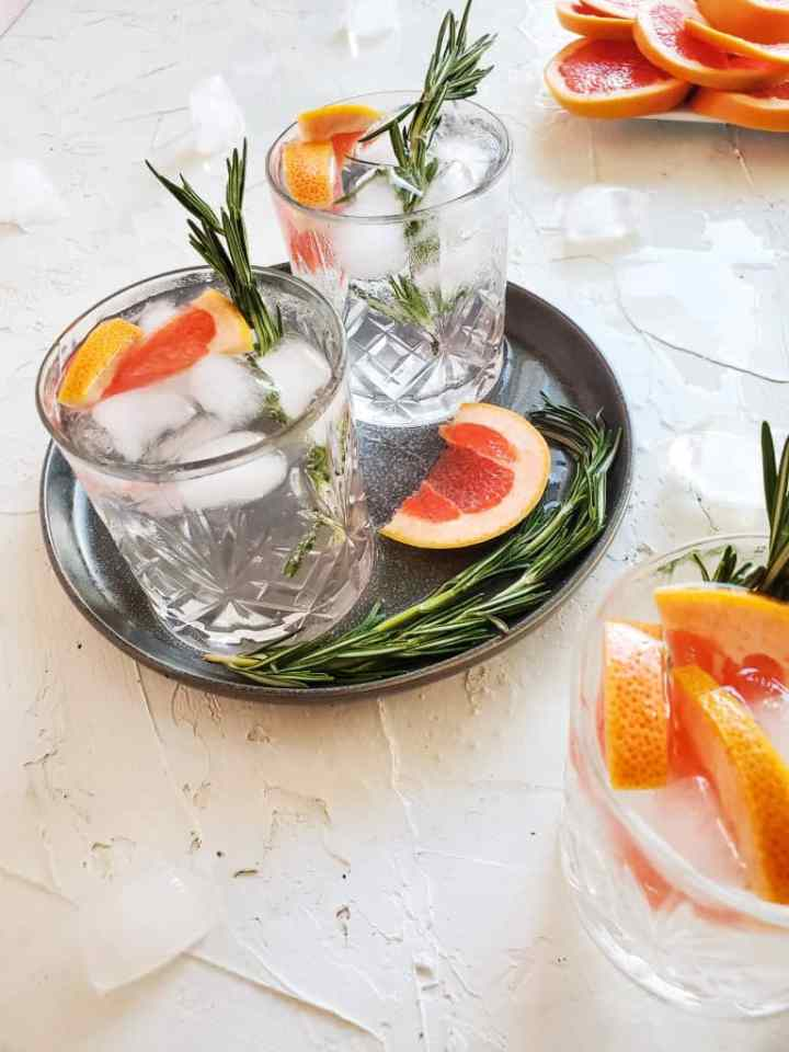 A picture of this cocktail in three glasses with grapefruit and rosemary granish