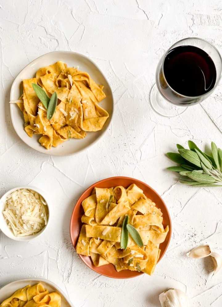 Pumpkin Sage Pasta plated with a bowl of vegan cheese