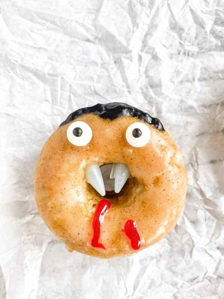 Close up of Vampire Vanilla Vegan Donut with eyes, fangs and blood driping