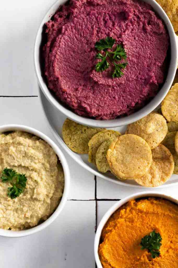 three bowls of carrot hummus in multiple colors (purple yellow and orange) with chips around it on a white surface