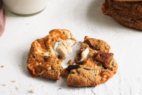Vegan S'more Cookies on a white surface being pulled apart