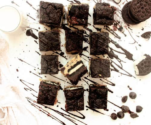 Vegan Slutty Brownies (12) in a row with melted chocolate drizzle on top, oreos on the side, and milk. They are on a white surface