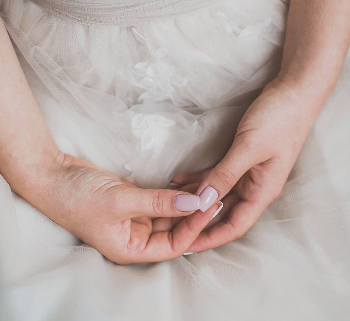Woman's hands in lap, wearing a wedding dress