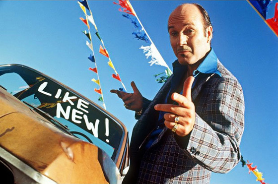 A used car salesman in a wacky suit points skeazily at the camera. A car in the background has paint on its windshield that reads 'Like New!'