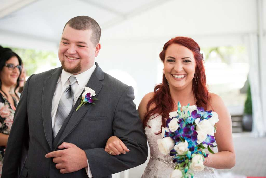happy couple walk down the aisle at their wedding