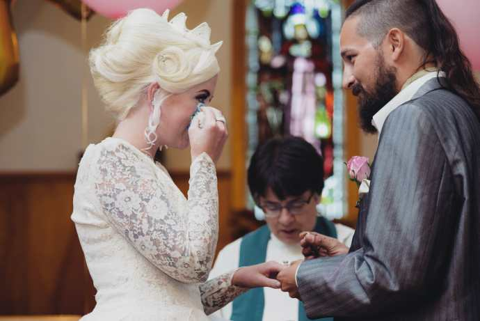 bride wipes away a tear as groom says vows