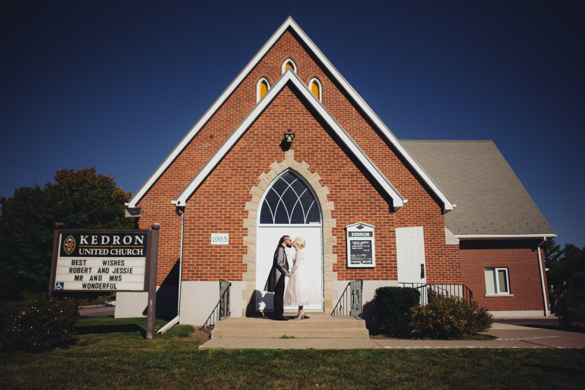 newlyweds kiss in front of kedron united church