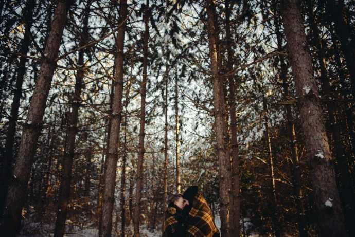 couple under blanket in greenwood forest