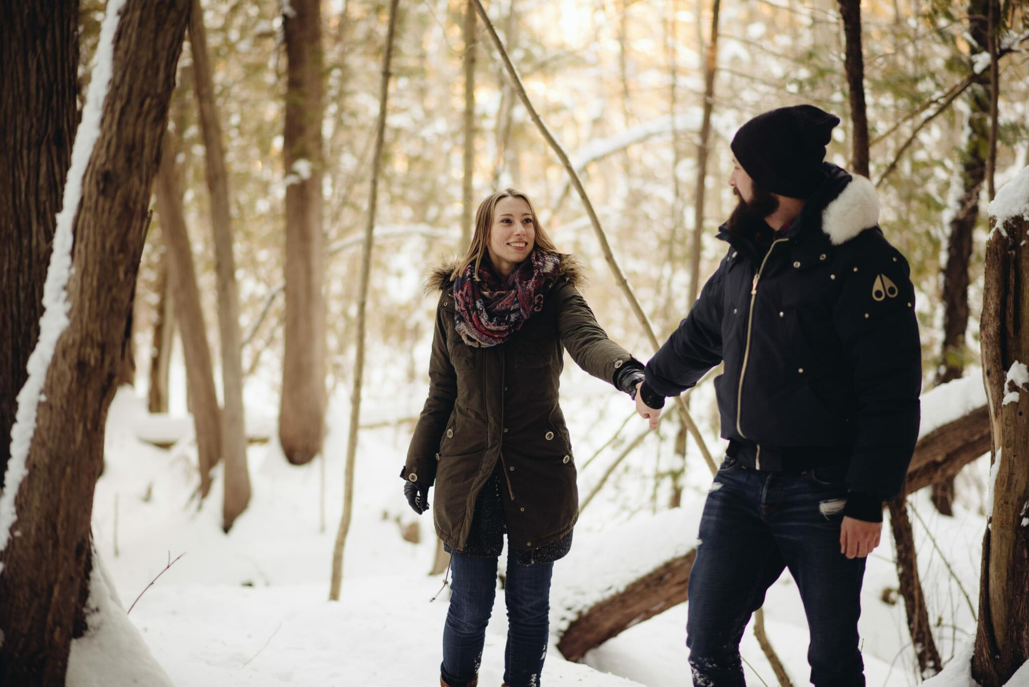 boyfriend leading girlfriend on trail in greenwood
