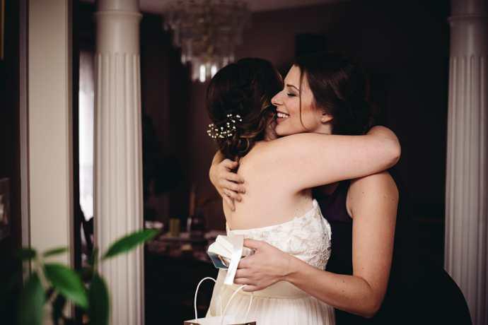 bride hugs bridesmaid at st leo church brooklin wedding