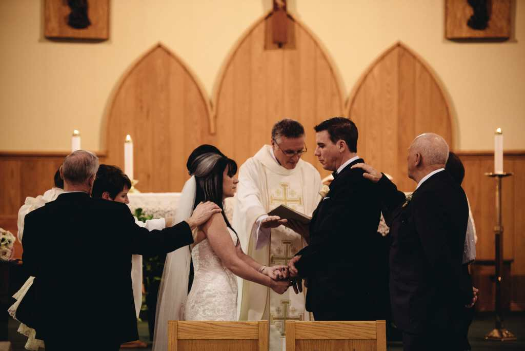 surrounded by family during wedding ceremony