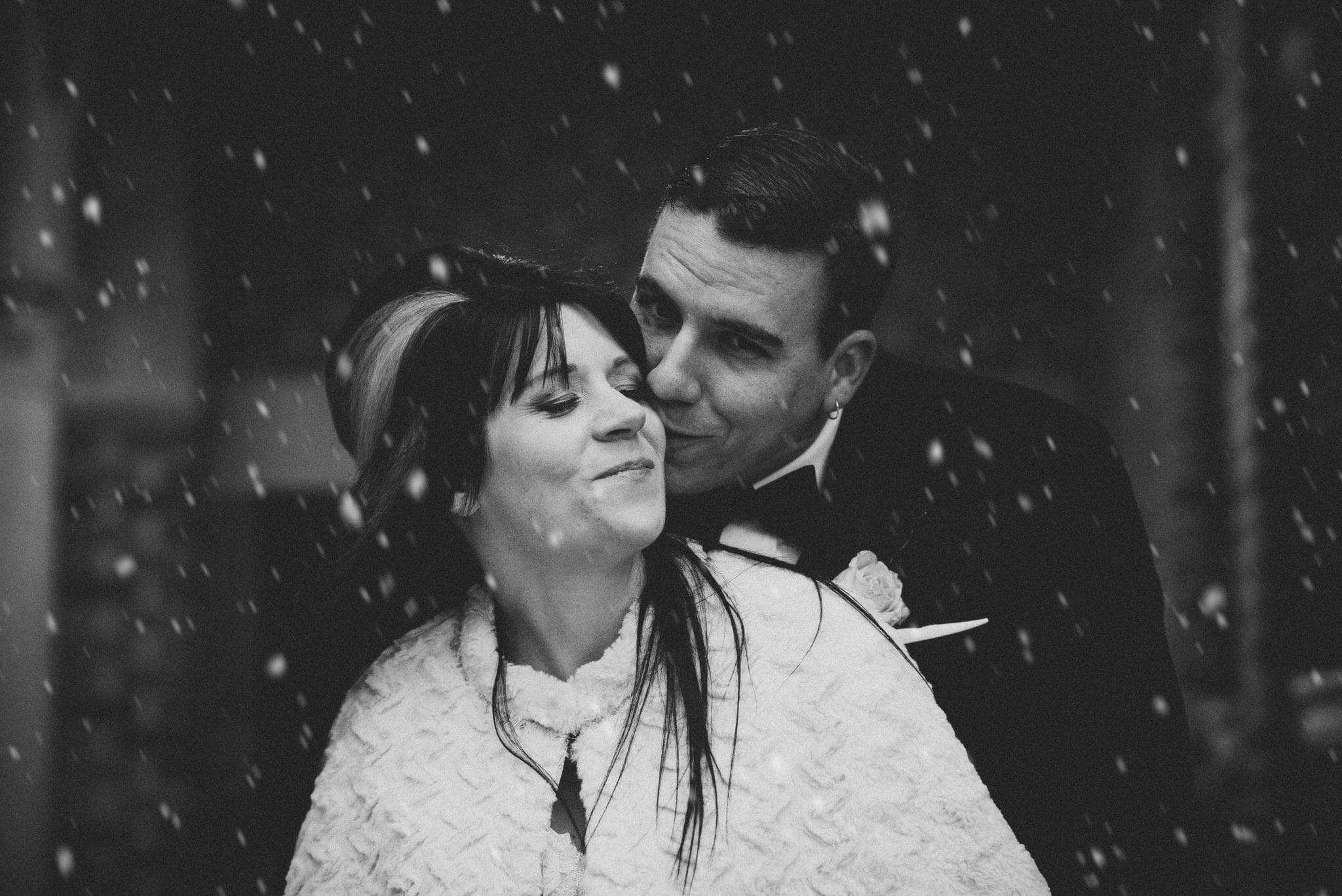 groom kisses brides cheek in the snowfall