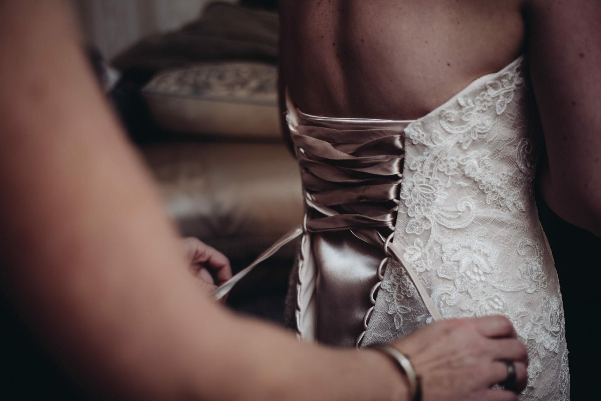 sister doing up bride wedding dress