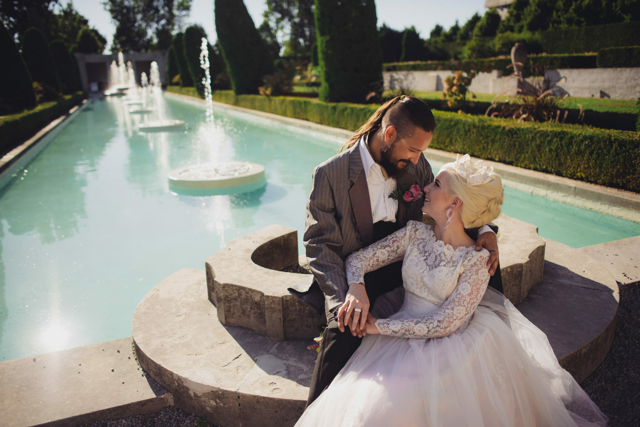 newlyweds in front of fountain pool at parkwood estate