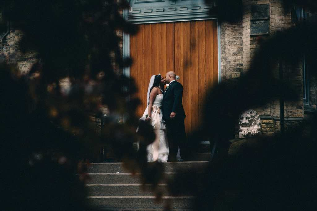 bride and groom photographed through trees