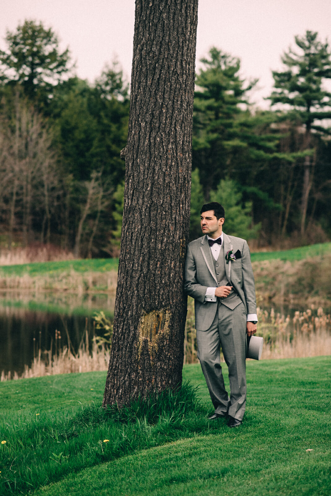 groom standing against tree at trillium trails