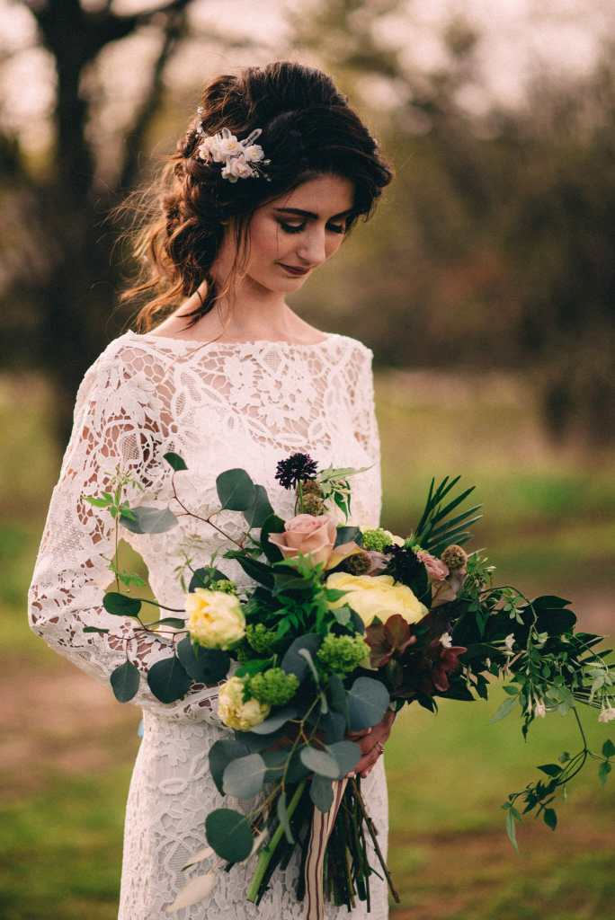 bride looking at her large bridal bouquet
