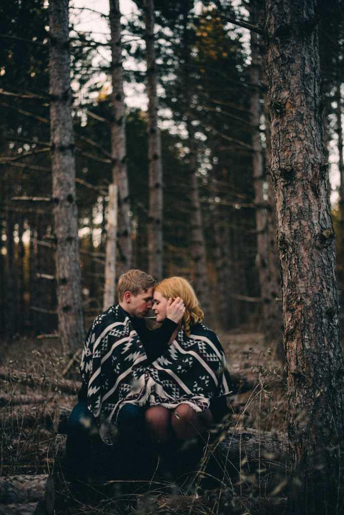 couple cuddles under blanket in forest