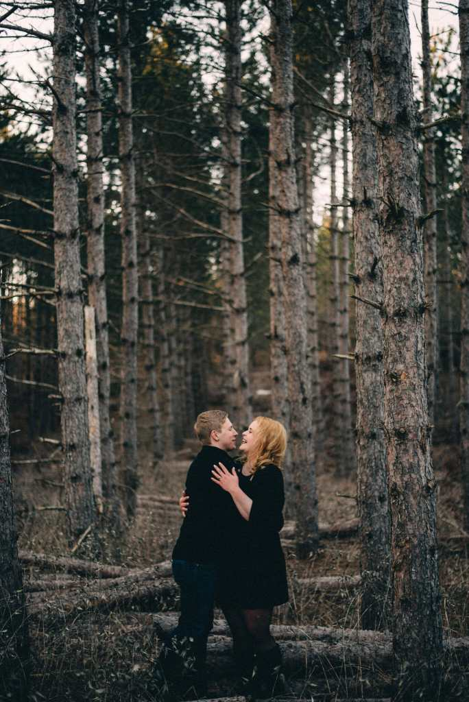 engaged couple laughs in forest at long sault conservation area