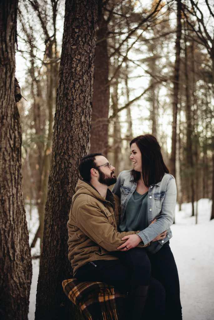 boyfriend and girlfriend sit together in forest